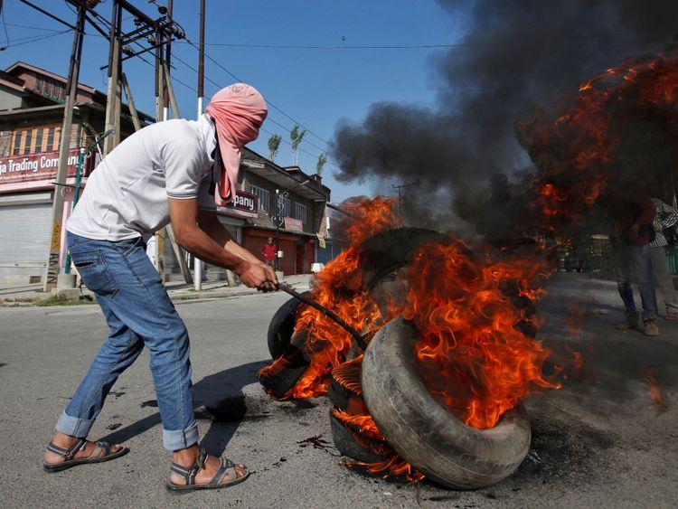 Un manifestant masqué brûle des pneus lors des funérailles de Kaisar Ahmad Bhat à Srinagar