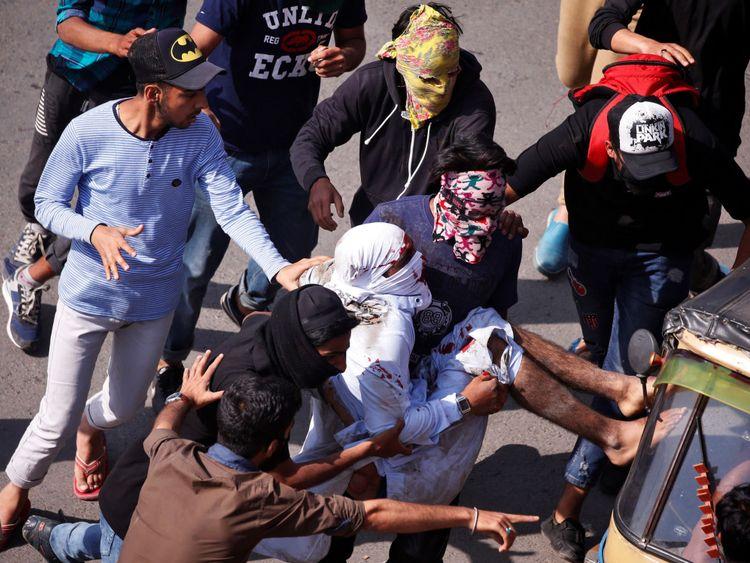 Les manifestants transportent un homme blessé un véhicule de la Force centrale de police de réserve (CRPF)