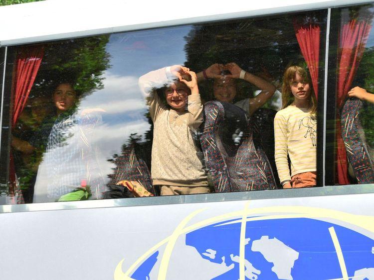 Les élèves en voyage scolaire regardent depuis leur bus car ils doivent rester dans le parking