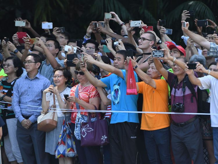 ystanders observent et prennent des photos du cortège transportant le président américain Donald Trump (non représenté) alors qu'il se dirige vers l'Istana, la résidence officielle du Premier ministre singapourien