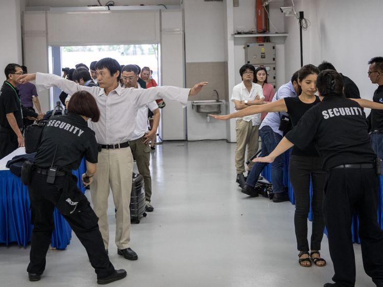Les membres de la presse locale et internationale font l'objet d'un contrôle de sécurité après être arrivés au centre des médias avant l'arrivée du président américain Donald Trump et du dirigeant nord-coréen Kim Jong-un le 10 juin 2018