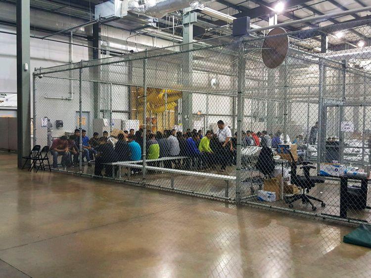 Les gens s'assoient sur des bancs à l'intérieur d'une cage dans l'établissement