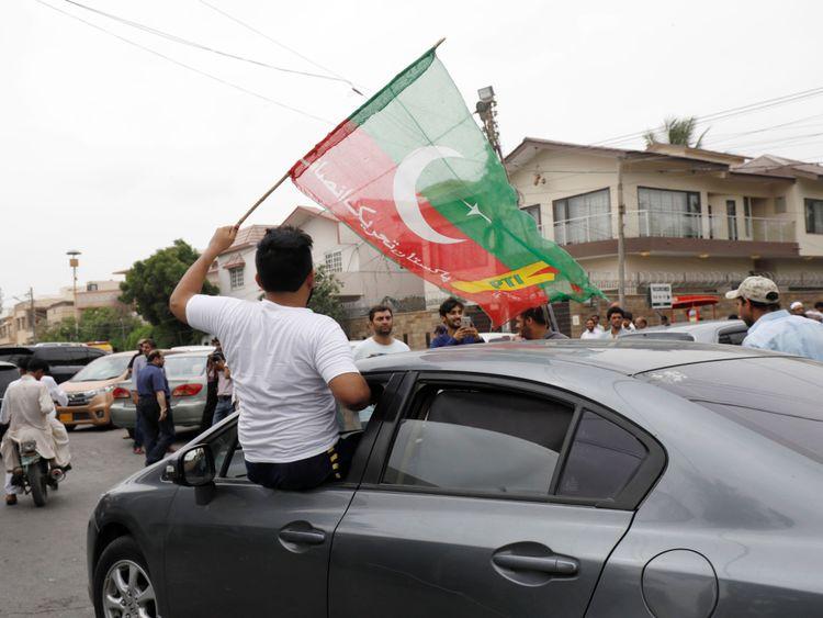 Un partisan du Pakistan Tehreek-e-Insaf (PTI) brandit le drapeau du parti depuis la fenêtre d'une voiture devant un bureau de vote lors des élections générales à Karachi, au Pakistan, le 25 juillet 2018. REUTERS / Akhtar Soomro
