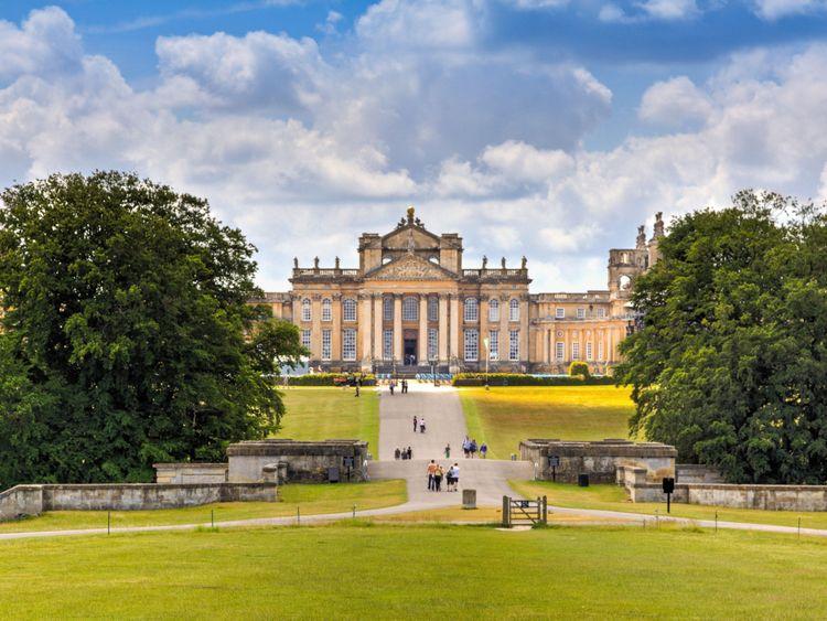 Woodstock, Royaume-Uni - 27 juin 2015: Blenheim Palace, Woodstock, Oxfordshire, Angleterre. C'est la résidence principale des ducs de Marlborough, et a été construite entre 1705 et 1722. Elle est employée comme maison de famille, mausolée et monument national. Le palais était aussi le lieu de naissance de Sir Winston Churchill. Un ciel bleu avec des nuages, une pelouse paysagée, des arbres verts et des touristes visitant le palais sont dans l'image.