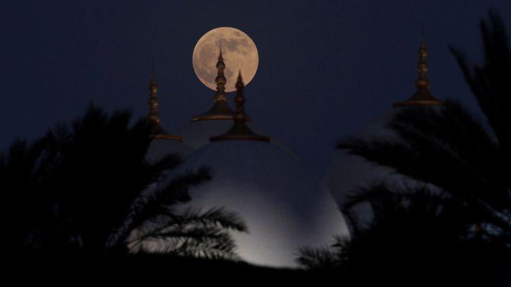 """Une éclipse lunaire d'une pleine """"Lune de sang"""" se lève derrière la grande mosquée Sheikh Zayed à Abu Dhabi, aux Émirats arabes unis le 27 juillet 2018. REUTERS / Christopher Pike"""