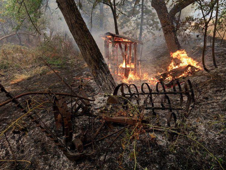 Une structure en bois brûle sur le bord sud du Carr Fire près d'Igo, en Californie