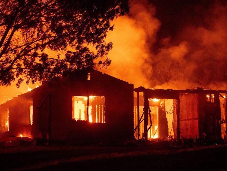 Une maison brûle pendant l'incendie de Carr à Redding, en Californie