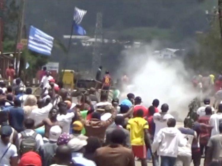 Les manifestants brandissent des drapeaux ambazoniens à mesure qu'ils avancent vers des barricades et la police au milieu des gaz lacrymogènes dans la ville anglophone de Bamenda