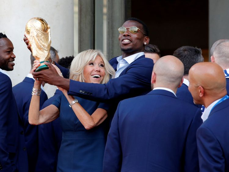 Brigitte Macron et le milieu de terrain Paul Pogba tiennent le trophée