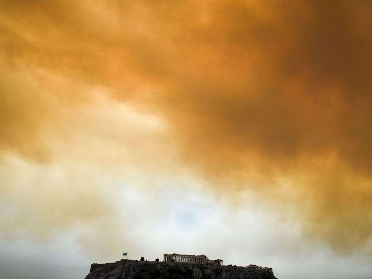 Le temple du Parthénon à Athènes alors que la fumée jaillit en arrière-plan
