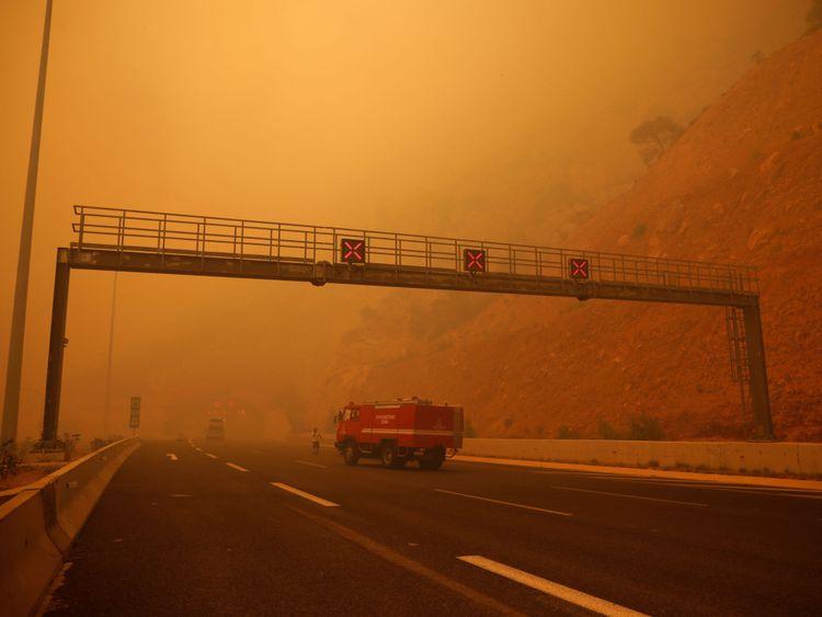 La fumée recouvre une autoroute alors qu'un feu brûle à Kineta, près d'Athènes
