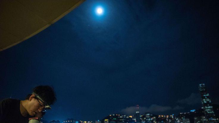 Les gens installent les télescopes pour observer l'éclipse lunaire à Tsim Sha Tsui à Hong Kong