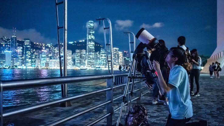 Des gens installent des télescopes pour observer l'éclipse lunaire à Hong Kong