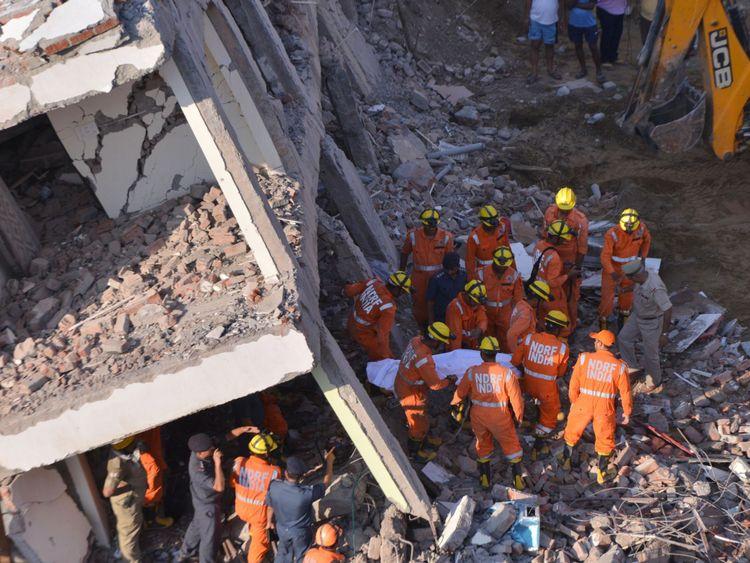 Les membres de la Force nationale de réaction aux catastrophes retirent une victime des décombres