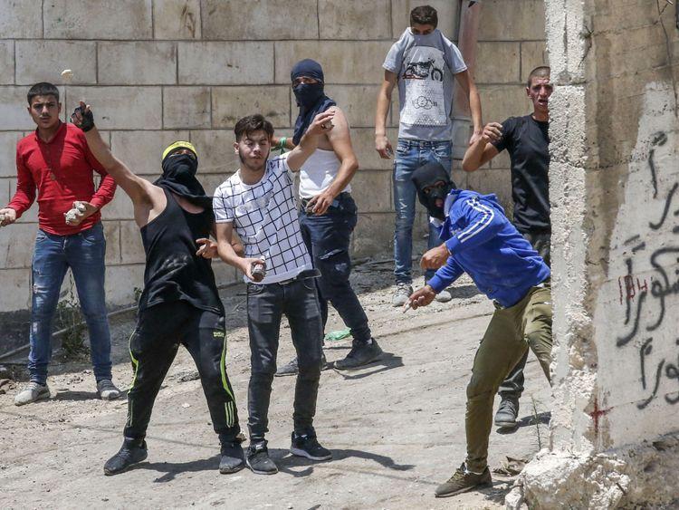 Des manifestants palestiniens lancent des pierres lors d'affrontements avec les forces de sécurité israéliennes à la suite d'un enterrement dans le village de Beit Ummar, au nord d'Hébron, dans la ville occupée de Cisjordanie le 14 juillet 2018. (Photo: HAZEM BADER / AFP / Getty Images)