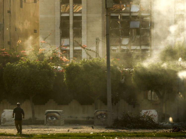 Un homme passe devant un bâtiment endommagé par une frappe aérienne israélienne dans la ville de Gaza le 14 juillet 2018. - L'armée israélienne a déclaré avoir lancé des frappes aériennes contre le Hamas dans la bande de Gaza le 14 juillet alors que des roquettes et des mortiers étaient lobés dans le sud d'Israël à partir de l'enclave palestinienne bloquée. (Photo par MAHMUD HAMS / AFP) (Crédit photo devrait lire MAHMUD HAMS / AFP / Getty Images)