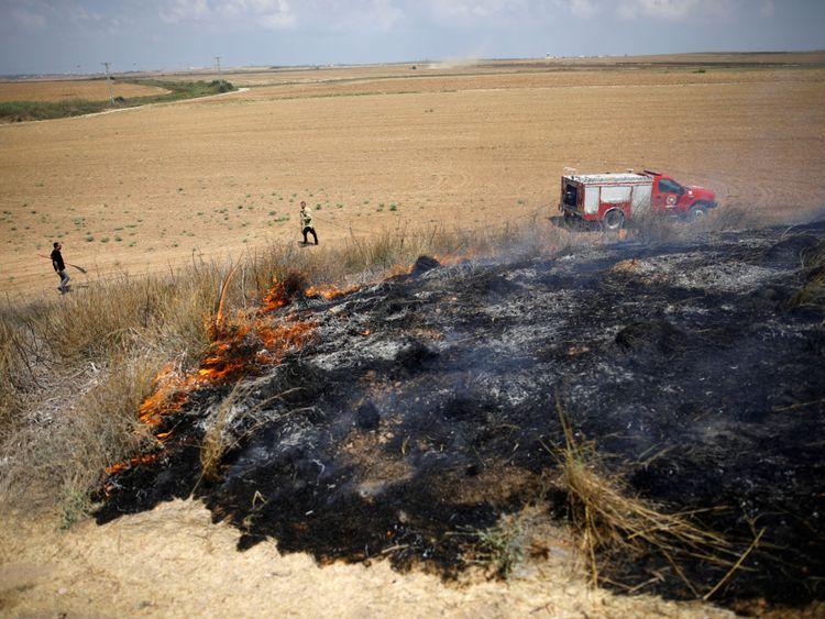 Des pompiers israéliens tentent d'éteindre un feu de brousse dans une région où les Palestiniens causent des flammes en faisant voler des cerfs-volants et des ballons chargés de matériaux inflammables, du côté israélien de la frontière entre Israël et la bande de Gaza 20 juillet