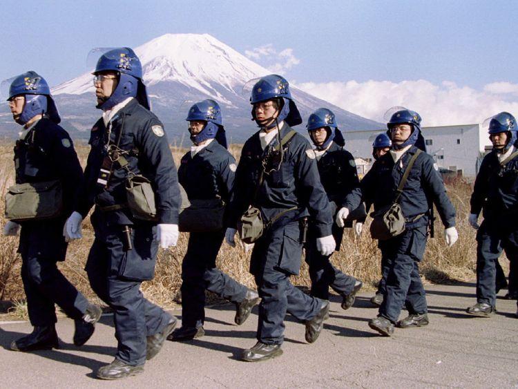 Une équipe de police quitte un complexe Aum Shinri Kyo (Suprême Truth Sect) après avoir terminé leur quart de travail dans le petit village de Kamikuishiki au pied du mont Fuji dans cette photo du 28 mars 1995