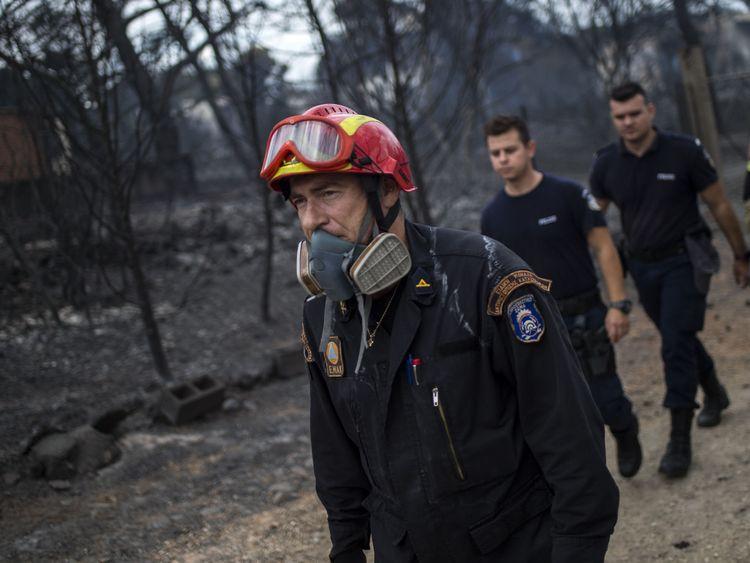 Les sauveteurs arrivent dans la zone où des cadavres ont été retrouvés suite à un incendie dans le village de Mati, près d'Athènes, le 24 juillet 2018