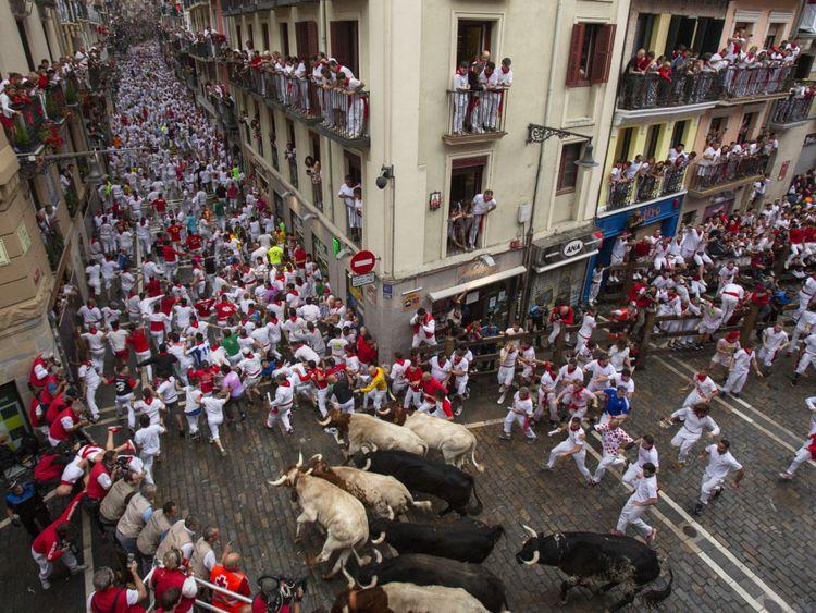 Des centaines de personnes prennent part à la course des taureaux chaque jour pendant San Fermin