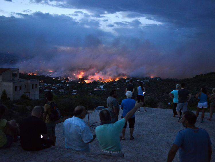 Les gens regardent un feu de forêt dans la ville de Rafina, près d'Athènes, le 23 juillet 2018