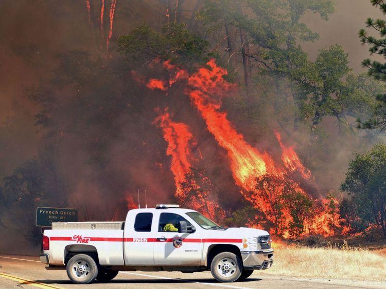 Les flammes engloutissent des arbres près d'une route pendant l'incendie de Carr à Redding