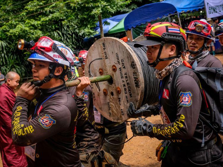 Les secouristes transportent de l'équipement dans le complexe de la grotte
