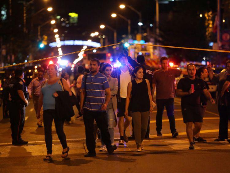 Les gens quittent une zone enregistrée par la police près de la scène d'un tir de masse à Toronto, Canada, 22 juillet 2018