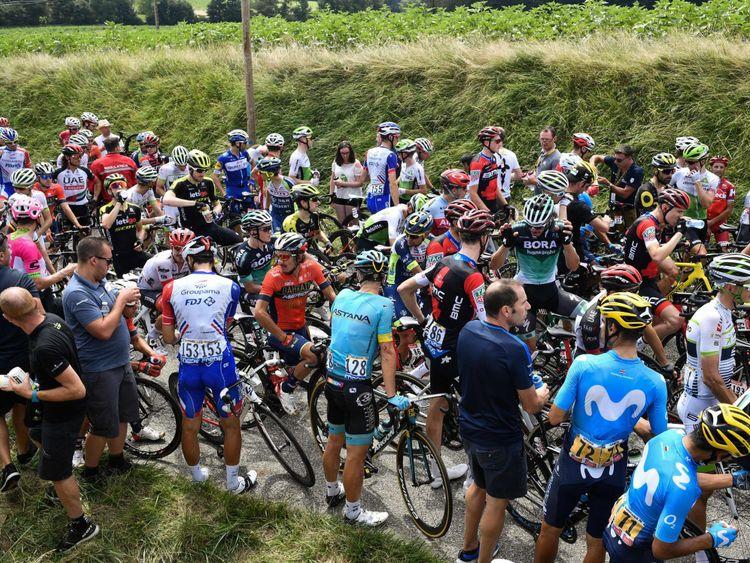 Le groupe de coureurs attend que l'étape reprenne, après que le gaz lacrymogène ait été utilisé pendant une campagne. protestation