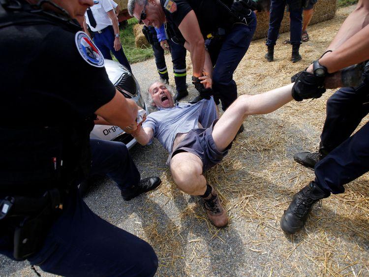 Les policiers portent un manifestant sur la route