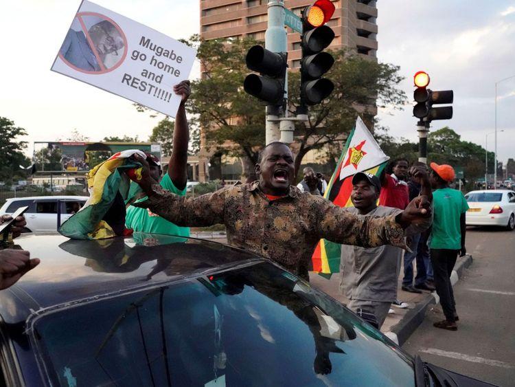 Les gens célèbrent dans les rues après la démission du président du Zimbabwe Robert Mugabe