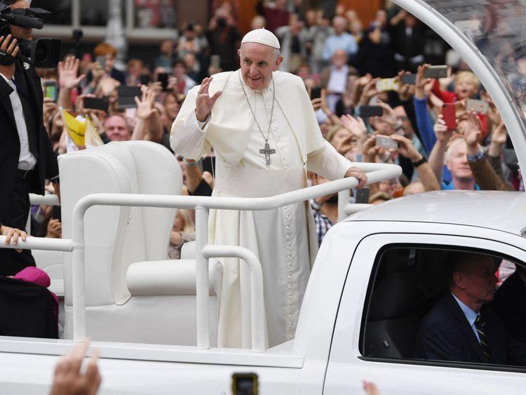 Le pape François accueille le public alors qu'il traverse Dublin dans la Popemobile