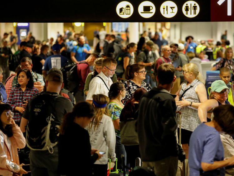 Des passagers d'Air Alaska attendent dans le terminal à la suite d'un incident au cours duquel un employé de la compagnie aérienne a décollé dans un avion à l'aéroport international de Seattle-Tacoma à Seattle, Washington, 10 août 2018.