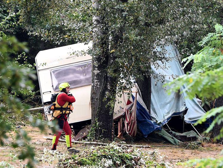 Un sauveteur marche devant une caravane endommagée dans le sud de la France