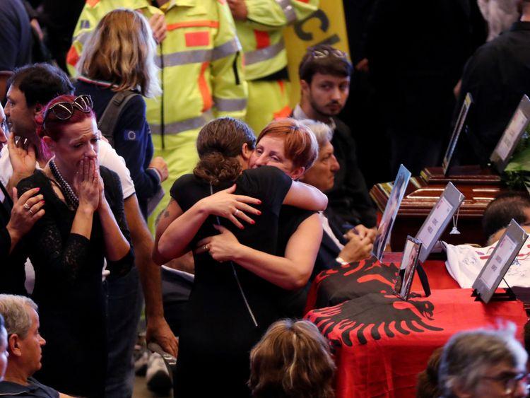 Des familles s'embrassent à côté des cercueils des victimes de l'effondrement du pont de Gênes