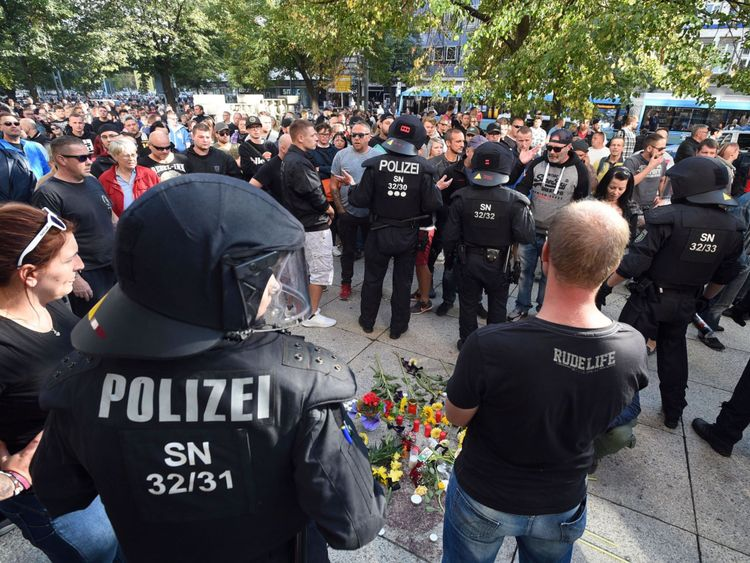 La police anti-émeute et des citoyens se tiennent à côté d'un mémorial de fortune pour un homme qui a été poignardé à mort