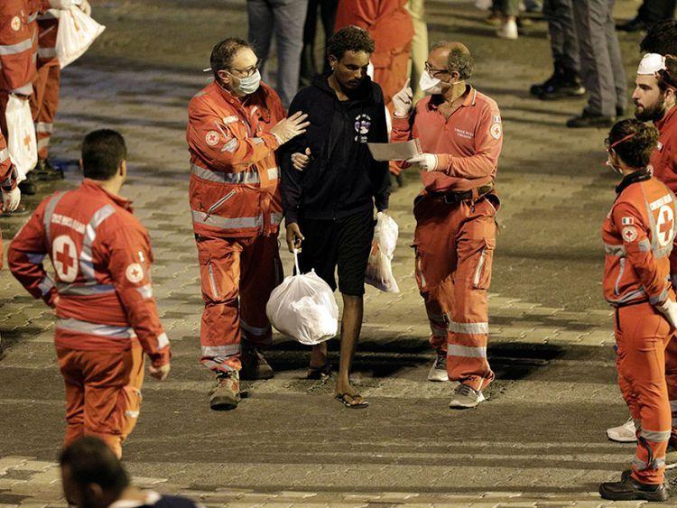 Un membre de la Croix-Rouge aide un migrant après avoir débarqué du navire des gardes-côtes italiens