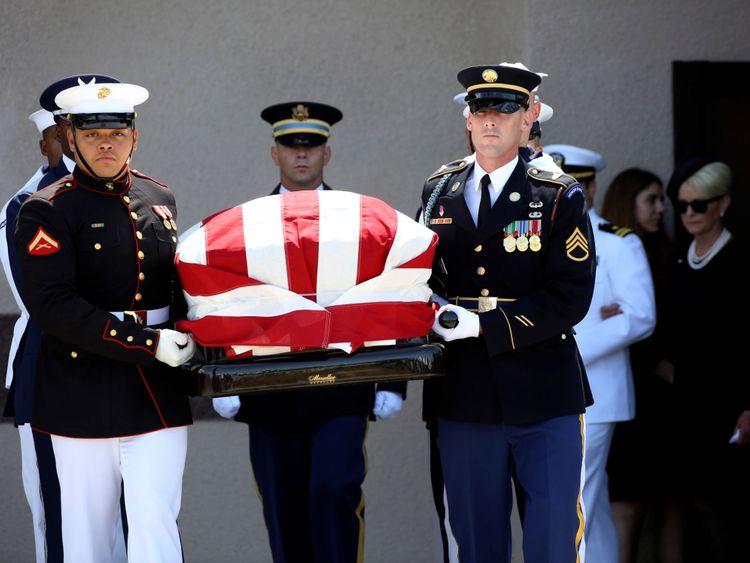 La famille McCain suit alors que des porteurs militaires transportent le cercueil du sénateur hors de l'église de Phoenix.