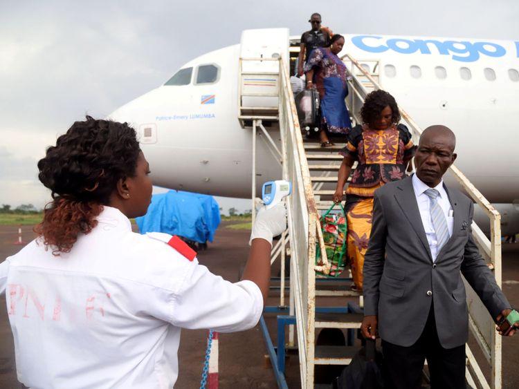 Des agents de santé congolais vérifient la température des passagers débarquant d'un avion de la compagnie Congo Airways à Mbandaka, en République démocratique du Congo 19 mai 2018