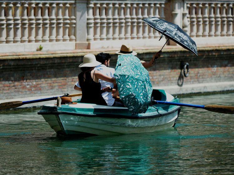 Les gens à l'ombre des parasols lors d'une promenade en bateau à Séville