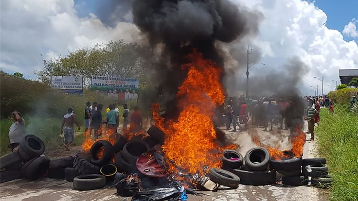 Les habitants de la ville frontalière brésilienne de Pacaraima brûlent des pneus et des effets personnels d'immigrants vénézuéliens après avoir attaqué leurs deux principaux camps de fortune