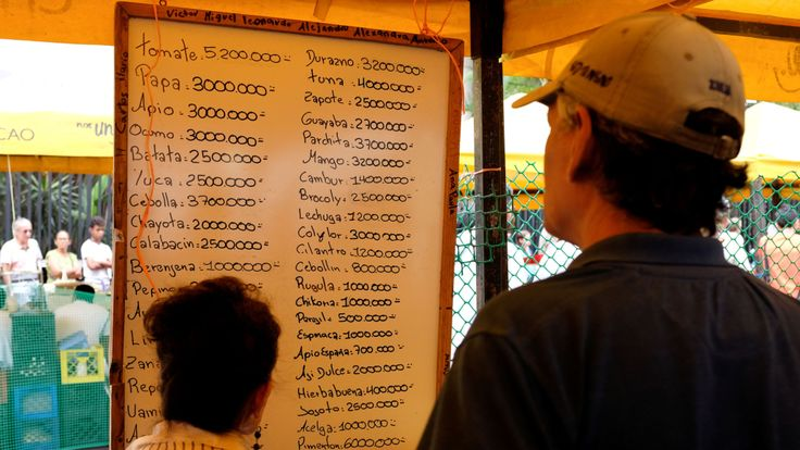 Les gens vérifient les prix des fruits et légumes dans un marché de rue à Caracas, au Venezuela