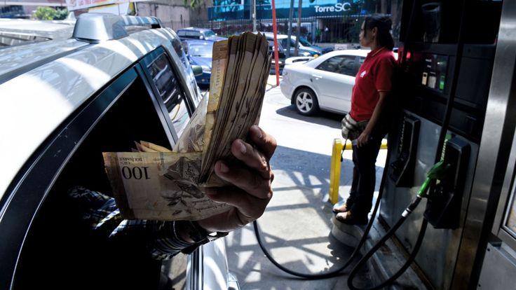 Un client montre des factures Bolivar dans une station-service à Caracas où les gens font la queue pour de l'essence