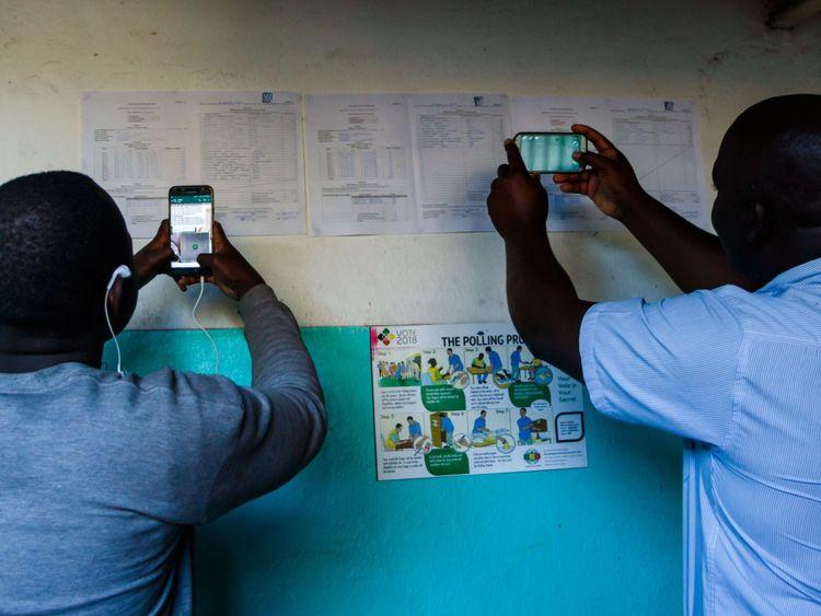 Les gens prennent des photos des résultats dans un bureau de vote du canton de Kambuzuma, Harare  résultats du dépouillement des votes à l'extérieur d'un bureau de vote dans le canton de Kambuzuma, Harare