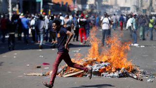 Un homme qui se porte candidat à la défense du parti d'opposition Mouvement pour le changement démocratique (MDC) de Nelson Chamisa brûle des barricades à Harare, au Zimbabwe
