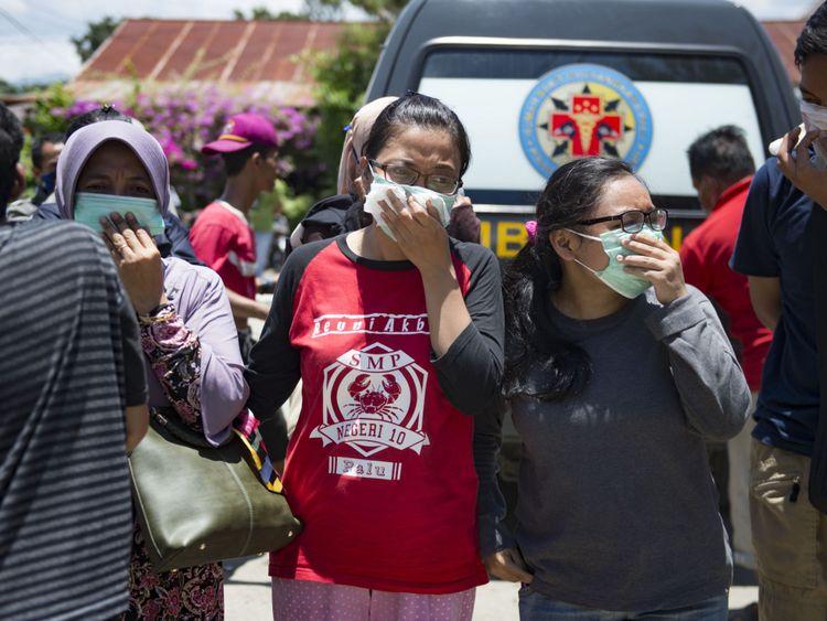 Les gens portent des masques lorsqu'ils tentent d'identifier les corps de leurs proches dans les locaux d'un hôpital de police