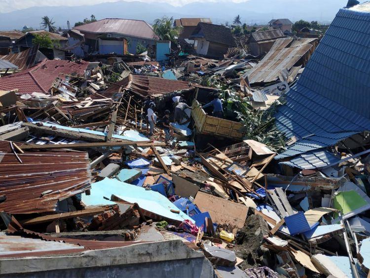 À la suite d'un tremblement de terre et d'un tsunami à Palu, dans le Sulawesi central, des personnes fouillent des débris dans un quartier résidentiel