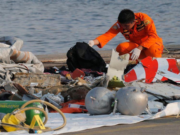 Un membre de l'Agence indonésienne de recherche et de sauvetage (BASARNAS) inspecte des débris présumés d'un avion de ligne Lion Air qui s'est écrasé au large de l'île de Java au port de Tanjung Priok à Jakarta, en Indonésie, le lundi 29 octobre 2018. Un avion Lion Air s'est écrasé dans la mer. quelques minutes après le décollage lundi de la capitale indonésienne contre le bilan de sécurité du pays après la levée des interdictions de ses compagnies aériennes par l'Union européenne et les États-Unis (AP Photo / Tatan Syufla