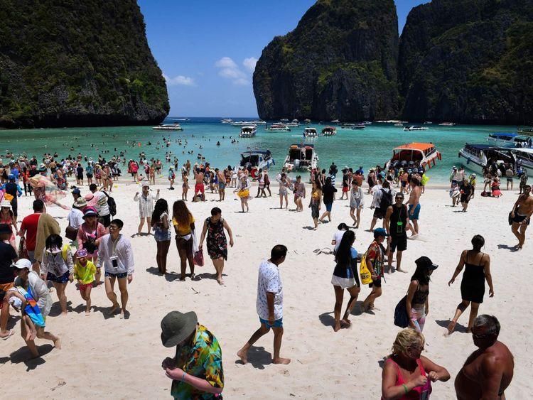 Cette photo prise le 9 avril 2018 montre une foule de touristes sur la plage de Maya Bay, sur l'île de Koh Phi Phi, dans le sud de la Thaïlande. Dans toute la région, les plages autrefois vierges de l'Asie du Sud-Est sont émues par des décennies de tourisme incontrôlé, alors que les gouvernements se démènent pour faire face aux eaux chargées de déchets et à la dégradation de l'environnement sans percer le moteur économique. / AFP PHOTO / Lillian SUWANRUMPHA / ALLER AVEC AFP STORY & # 39; THAÏLANDE-INDONÉSIE-PHILIPPINES-TOURISME-ENVIRONNEMENT & # 39; par Lillian SUWANRUMPHA avec Joe
