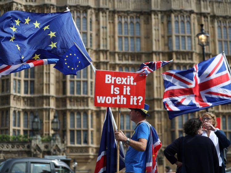 Un démonstrateur tient une pancarte indiquant «Brexit». Cela en vaut-il la peine? & # 39; alors qu'il était drapé sous les drapeaux de l'Union européenne (UE) et de l'Union, alors qu'il protestait devant les chambres du Parlement au centre de Londres le 10 septembre 2018